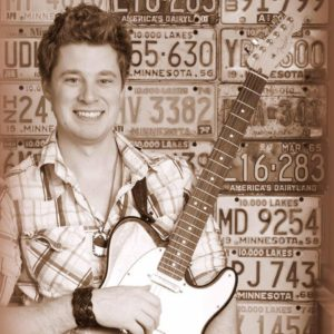 Neal Elder posing with a guitar